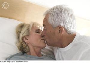 Mature_man_kissing_woman_in_bed_013610bl